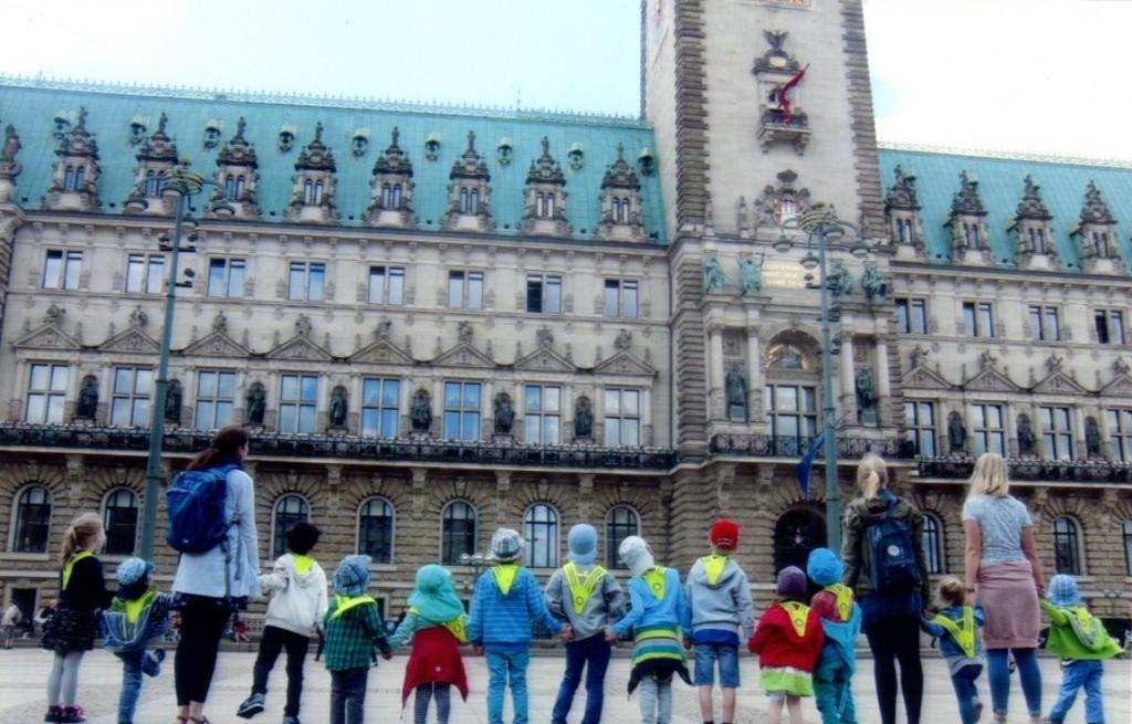 Die Kinder bestaunen während ihres Ausflugs zum Zoologischen Museum das Hamburger Rathaus.